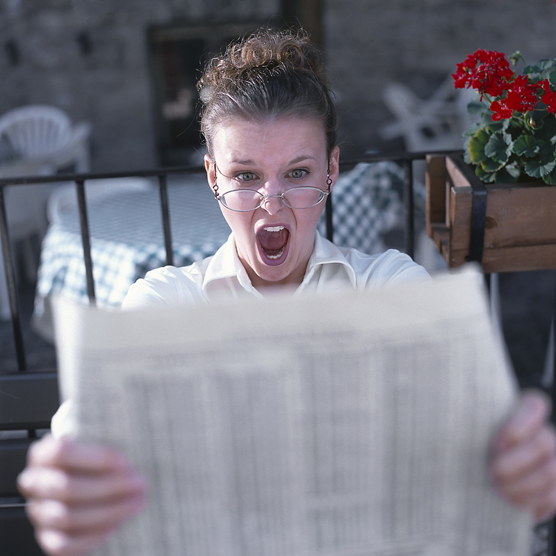 Woman reading newspaper screaming.jpg