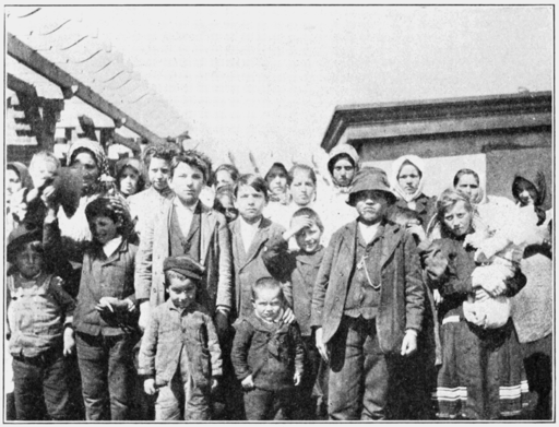 Ellis Island.Immigrants.PSM_V80_D392_Cosmopolitan_group_on_the_roof_of_the_detention_quarters.png